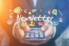 Concept of man holding futuristic interface with newsletter titl. E and multimedia icons flying all around - Internet concept Stock Images