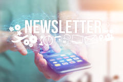 Concept of man holding futuristic interface with newsletter titl. Concept view of man holding futuristic interface with newsletter title and multimedia icons Royalty Free Stock Photo