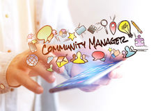 Concept of man holding smartphone with community manager title a. Concept view of man holding smartphone with community manager title and multimedia icons flying Royalty Free Stock Photos
