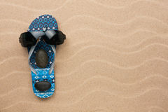 Concept of a man's face, flip-flops and sunglasses Stock Image