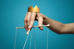 Concept of manipulation. Hand with crown holds strings for manipulation on blue background stock photo