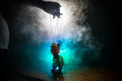 Concept of manipulation. Hand holds strings for manipulation. The hand controls the puppet strings on a dark foggy background. Selective focus royalty free stock photos