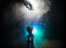 Concept of manipulation. Hand holds strings for manipulation. The hand controls the puppet strings on a dark foggy background. Selective focus stock image