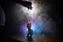 Concept of manipulation. Hand holds strings for manipulation. The hand controls the puppet strings on a dark foggy background. Selective focus stock photography