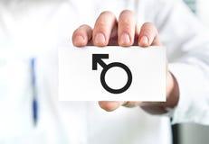 Concept masculin de santé Docteur tenant la carte de visite professionnelle de visite avec le symbole de l'homme Urologue ou spéc image stock