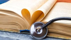 Concept of medical education with book and stethoscope. treatment of patients. close up stock photo