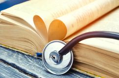 Concept of medical education with book and stethoscope. treatment of patients. close up.  stock photos