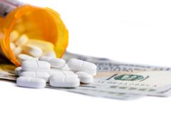 Concept for medical expenses. Close up of a prescription bottle with white tables falling out on top of a group of hundred dollar bills Stock Photos