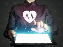 Concept of medical services, diagnosis and treatment. Image of a girl with tablet pc in her hands and heart rate icon. Concept of medical services, diagnosis Stock Photos