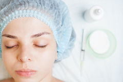 Concept of medical treatment of rejuvenation and skincare. Beautiful young woman in spa beauty salon before face treatment, with set of medical tools at white royalty free stock images