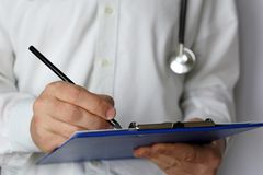 Doctor with stethoscope writes a prescription paper, medical exam. Concept of medicine, diagnosis, examination at the clinic, health care stock photography