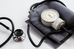 Concept for medicine. Vintage tonometer and stethoscope on white isolated background. View from above.  stock photography