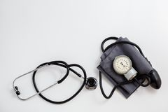 Concept for medicine. Vintage tonometer and stethoscope on white isolated background. View from above.  stock image