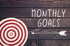 Concept mensuel de buts avec le panneau de dard sur le mur en bois foncé images stock