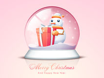 Concept of Merry Christmas and Happy New Year celebrations. Cute snowman in Santa cap and scarf with gift box in a snow dome on pink background for Merry Stock Image