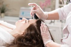 The concept of mesotherapy. Thrust to strengthen the hair and their growth. Handsome woman receives an injection in the head. The procedure makes doctor in white Stock Images