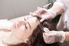 The concept of mesotherapy. Thrust to strengthen the hair and their growth. Handsome woman receives an injection in the head. The procedure makes doctor in white Stock Photo