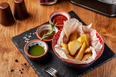 The concept of Mexican cuisine. Baked spicy potatoes with pepper, with different sauces, salsa, guacamole, chilli and shrimp. Background image. copy space royalty free stock photo