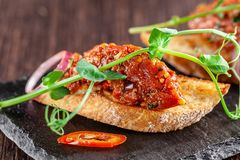 The concept of Mexican cuisine. Beef tartare with parsley, French mustard beans on baguette croutons. A dish in the restaurant. On a black stone slate royalty free stock photography