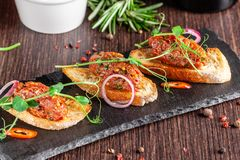 The concept of Mexican cuisine. Beef tartare with parsley, French mustard beans on baguette croutons. A dish in the restaurant royalty free stock photography