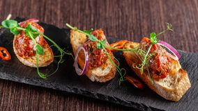 The concept of Mexican cuisine. Beef tartare with parsley, French mustard beans on baguette croutons. A dish in the restaurant. On a black stone slate royalty free stock photos