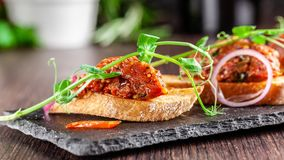 The concept of Mexican cuisine. Beef tartare with parsley, French mustard beans on baguette croutons. A dish in the restaurant. On a black stone slate royalty free stock image