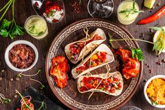 The concept of Mexican cuisine. Mexican food and snacks on a wooden table. Taco, sorbet, tartar, glass and bottle of red wine. Background image. Top view, copy royalty free stock photography
