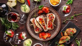 The concept of Mexican cuisine. Mexican food and snacks on a wooden table. Taco, sorbet, tartar, glass and bottle of red wine. Background image. Top view, copy stock photo