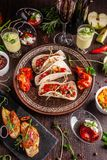 The concept of Mexican cuisine. Mexican food and snacks on a wooden table. Taco, sorbet, tartar, glass and bottle of red wine. Background image. Top view, copy royalty free stock image