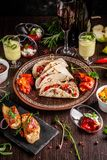 The concept of Mexican cuisine. Mexican food and snacks on a wooden table. Taco, sorbet, tartar, glass and bottle of red wine. Background image. Top view, copy royalty free stock images