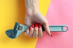 Concept minimal d'amusement Mains de femme avec la clé réglable, clé photos libres de droits