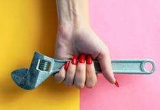 Concept minimal d'amusement Mains de femme avec la clé réglable, clé photo libre de droits