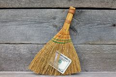 Concept of mismanagement. Broom stuck with dollars. On wooden background Stock Photos