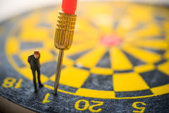Concept of missed target business strategy. Businessman looking at the untargeted arrow on dart board stock images