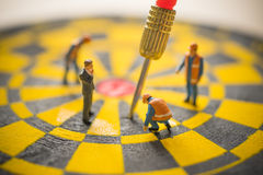 Concept of missed target business strategy. Worker diagnosis the untargeted arrow on dart board royalty free stock photo