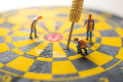 Concept of missed target business strategy. Worker diagnosis the untargeted arrow on dart board stock image