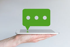 Concept of mobile chat and messaging service. Hand holding tablet or large smart phone. In front of grey background. Green messaging speech bubble with Royalty Free Stock Photo