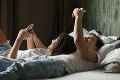 Concept mobile de dépendance, jeune couple utilisant les smartphones o menteur Photographie stock libre de droits