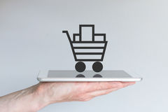 Concept of mobile online shopping. Hand holding tablet or large smart phone. In front of grey background. Shopping cart icon with reflections on smart phone Royalty Free Stock Image