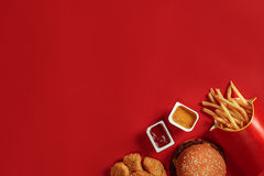 Concept of mock up burger, potatoes, sauce on red background. Copy space for text and logo. Flat lay Stock Photos