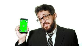 Concept mockup. Bearded businessman with glasses holding a green screen smartphone. stock video