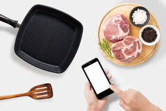 Concept of mockup using smartphone and raw pork chop steak, gril Stock Photos