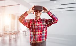 Concept of modern entertaining technologies with man wearing virtual reality mask Royalty Free Stock Images