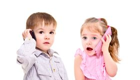 The concept of the modern generation of children. Cute little kids talking on a mobile phone isolated on white background royalty free stock photography