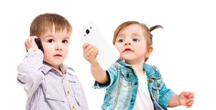The concept of the modern generation of children. Cute little kids with mobile phones isolated on white background royalty free stock photography