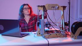Concept of modern production technologies. Young woman student makes the item on the 3D printer stock video footage