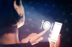Concept of modern technology in catering industry. Image of a girl with a smartphone in hands. She presses on the restaurant icon. Concept of modern technology Royalty Free Stock Image