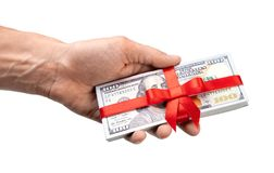 Concept, money as gift, win or bonus. Man`s hand takes or gives pile of 100 dollar bills tied with red ribbon with bow. Isolated. On white background stock images