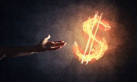 Concept of money making with dollar currency fire symbol on dark Stock Photography
