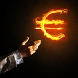 Concept of money making with euro currency fire symbol on dark background Stock Photography